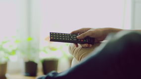Television remote control. Hand using television remote control stock footage