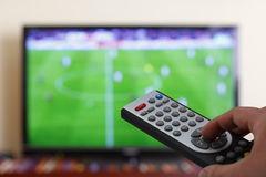 Television remote control in the hand, zapping. Watching a football match in the television, with a tv remote control in the hand Stock Image
