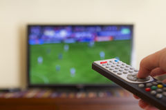 Television remote control in human hands. Watching a soccer match in the television, with a tv remote control in the hand Stock Photography