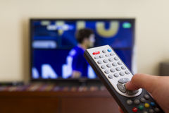 Television remote control in human hands. Watching a soccer match in the television, with a tv remote control in the hand Royalty Free Stock Photos