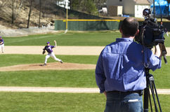 Television Reporter. A videographer records the action at a high school baseball game on a sunny day in Maine Stock Image