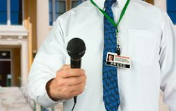 Television reporter with microphone and press pass news media identification card. In a bright white shirt and colorful blue tie closeup as he stands in front Stock Images