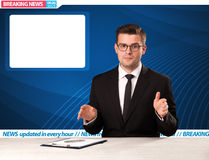 Television reporter telling breaking news at his studio desk wit Royalty Free Stock Photography