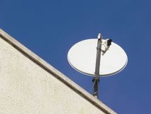 Television Satellite Dish. A white home satellite dish against a blue sky Stock Images