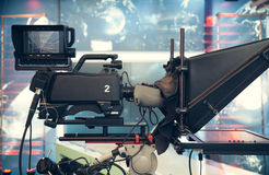 Television studio with camera and lights - recording TV NEWS. Shallow depth of field - focus on camera Stock Image