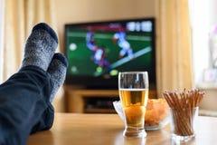 Television TV som håller ögonen på (fotbollsmatchen) med fot på tabellen och arkivbilder