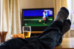 Television, TV watching (football match) with feet on table and. Huge amounts of snacks - stock photo Stock Photos