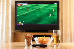 Television, TV watching (football, soccer match) with snacks lyi Stock Photography