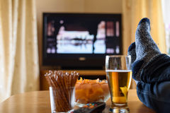 Television, TV watching (movie) with feet on table and huge amou Royalty Free Stock Photography