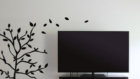 Television and Wall. Large, flat panel television against a decorated wall Royalty Free Stock Photography