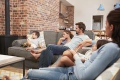 Televisione di sorveglianza del salotto di piano di Sit On Sofa In Open della famiglia Fotografia Stock Libera da Diritti