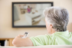 Televisione di sorveglianza dell'uomo usando telecomando Immagini Stock