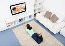 Televisione di sorveglianza della donna a casa Fotografia Stock