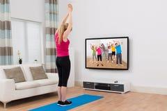Televisione di sorveglianza della donna ed esercitarsi a casa Fotografie Stock Libere da Diritti