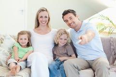 Televisione di sorveglianza della famiglia sul sofà immagine stock