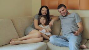 Televisione di sorveglianza della giovane famiglia che si siede sul sofà archivi video