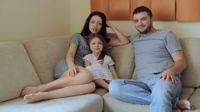 Televisione di sorveglianza della giovane famiglia che si siede sul sofà video d archivio