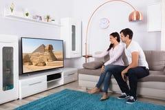 Televisione di sorveglianza delle coppie a casa fotografia stock libera da diritti