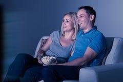 Televisione di sorveglianza delle coppie felici fotografia stock