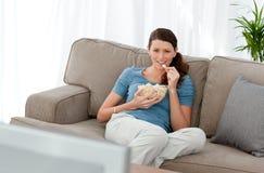 Televisione di sorveglianza e cibo della donna attraente Fotografia Stock