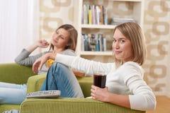 televisione due dell'adolescente degli allievi femminili che guarda Immagine Stock