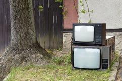 Televisiones en una pila cerca del árbol fotografía de archivo