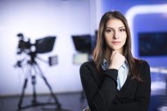 Televisionpresentatörinspelning i nyheternastudio Kvinnligt journalistankare som framlägger affärsrapporten som antecknar i telev Royaltyfria Bilder