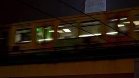 Televisiontorn med snö på natten och drev som lämnar och ankommer, Alexanderplatz station, Berlin, Tyskland stock video