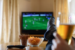 Televisão, tevê que olha (fósforo de futebol) com pés na tabela e Imagem de Stock