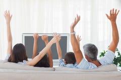 Televison e aumento di sorveglianza della famiglia il loro armi immagini stock