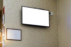Televisor op een muur met een leeg kader voor uw reclame stock afbeelding