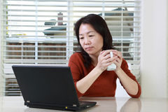 Telework. Woman working from home with laptop and coffee Stock Photo