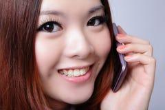 Teléfono celular de discurso de la mujer joven con sonrisa dulce Foto de archivo