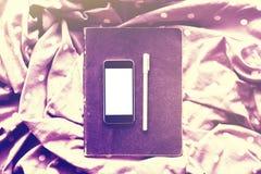 Teléfono celular en blanco con la pluma en el diario, efecto de la foto del instagram Fotos de archivo libres de regalías