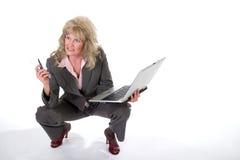 Teléfono celular y computadora portátil que hacen juegos malabares de la mujer de negocios Foto de archivo libre de regalías