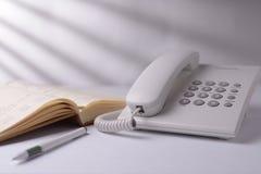 Teléfono con el libro abierto Fotografía de archivo libre de regalías