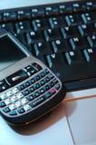 Teléfono de Pda en el teclado de la computadora portátil Imagenes de archivo