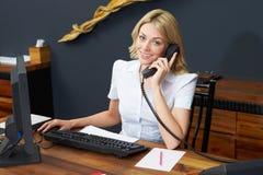 Teléfono de Using Computer And del recepcionista del hotel Fotografía de archivo libre de regalías