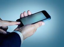 Teléfono elegante del teléfono elegante móvil de la prensa del tacto del hombre de negocios en fondo azul Foto de archivo