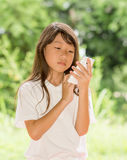 Teléfono elegante del uso de la muchacha de Asia en jardín Imágenes de archivo libres de regalías