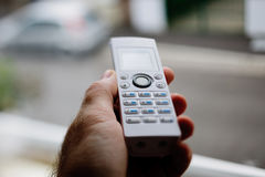 Teléfono inalámbrico a disposición contra ventana Imágenes de archivo libres de regalías
