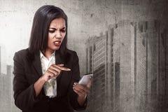 Teléfono móvil de mirada enojado de la mujer de negocios Imagen de archivo