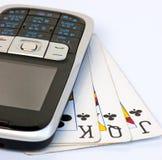 Teléfono móvil en 3 tarjetas que juegan usadas Fotografía de archivo libre de regalías