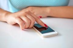 Teléfono móvil en una tabla blanca y una mujer joven Foto de archivo