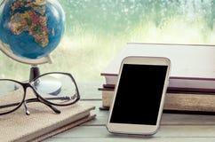 Teléfono móvil, teléfono elegante, teléfono con el libro, globo y lentes Imágenes de archivo libres de regalías