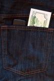 Teléfono móvil y un billete de banco del dólar en pantalones vaqueros Imagen de archivo libre de regalías