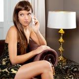 Teléfono que habla de la mujer de la manera de la elegancia en sofá Foto de archivo libre de regalías