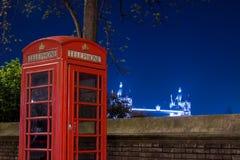 Teléfono y puente rojos en la noche, Londres, Inglaterra de la torre Imagen de archivo