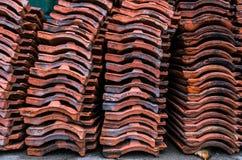 A telha de telhado velha vermelha pôs na pilha após a renovação velha do cortiço Imagem de Stock