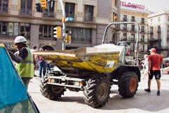 Telha em um quadrado, caminhão basculante pequeno da pilha dos trabalhadores imagem de stock royalty free